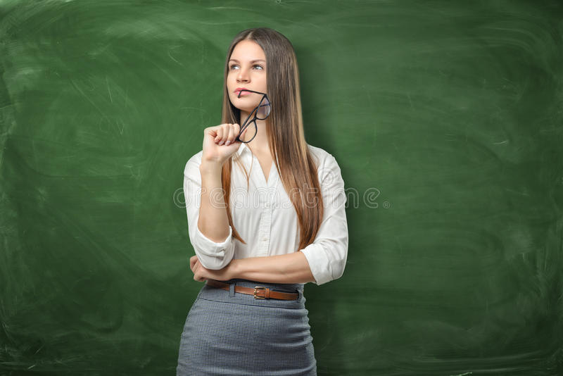 La mujer bonita joven está sosteniendo sus vidrios y está pensando en fondo verde de la pizarra imagenes de archivo