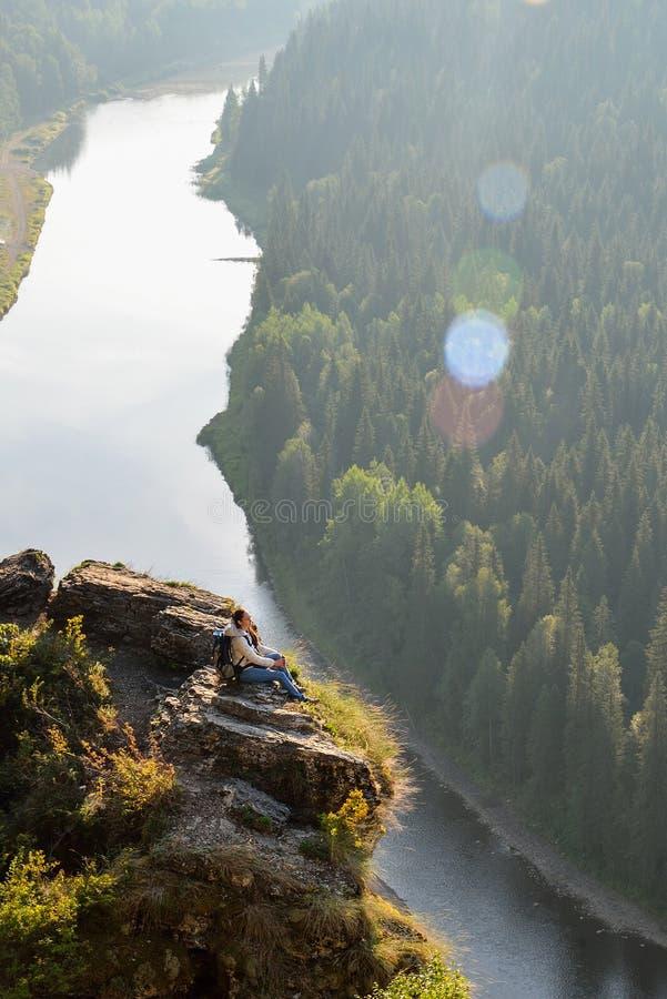 La mujer bonita joven que se sienta encima de la montaña, se relaja, calma y meditación con la naturaleza fotografía de archivo libre de regalías