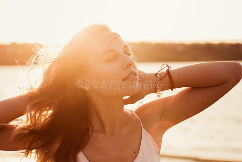 La mujer bonita joven relaja y goza del lago cercano al aire libre de los rayos de la puesta del sol fotos de archivo libres de regalías