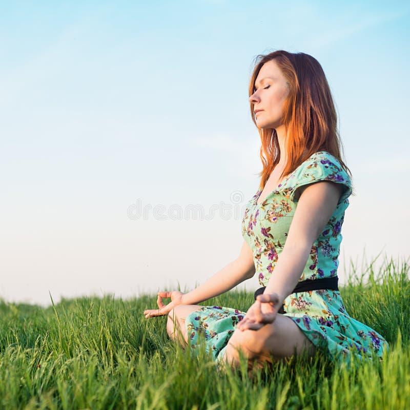 La mujer bonita medita en el parque fotografía de archivo libre de regalías