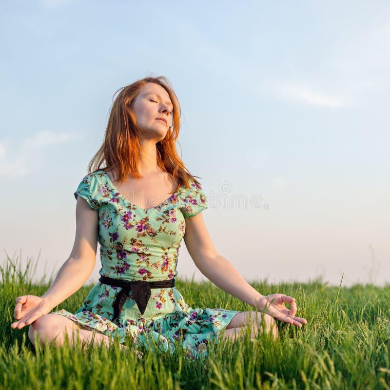 La mujer bonita medita en el parque imagen de archivo