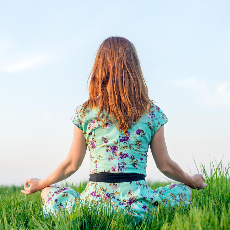 La mujer bonita medita en el parque foto de archivo