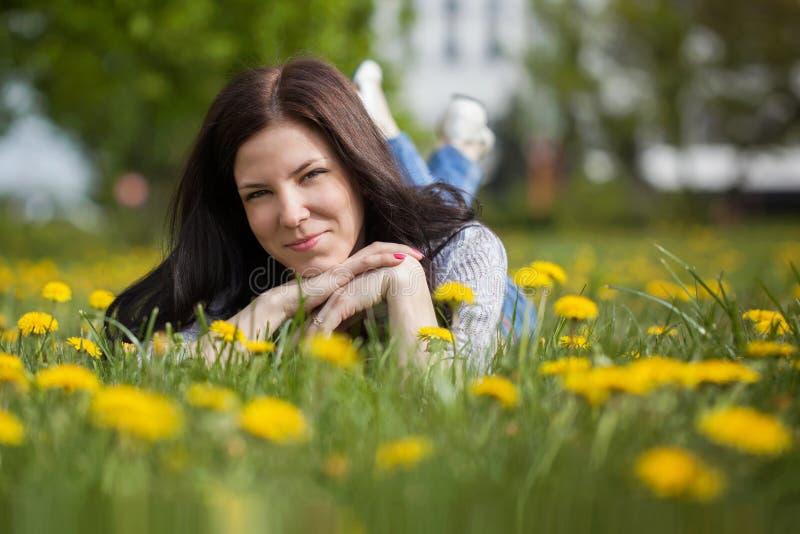 La mujer bonita que se acuesta en los dientes de león coloca, gir alegre feliz fotos de archivo libres de regalías