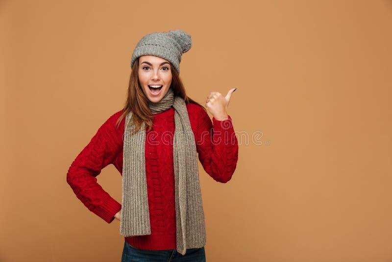 La mujer bonita salida feliz en invierno viste mostrar el pulgar encima de ges imagenes de archivo