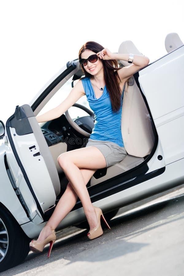 La mujer bonita se sienta en el coche con la puerta lateral abierta foto de archivo libre de regalías