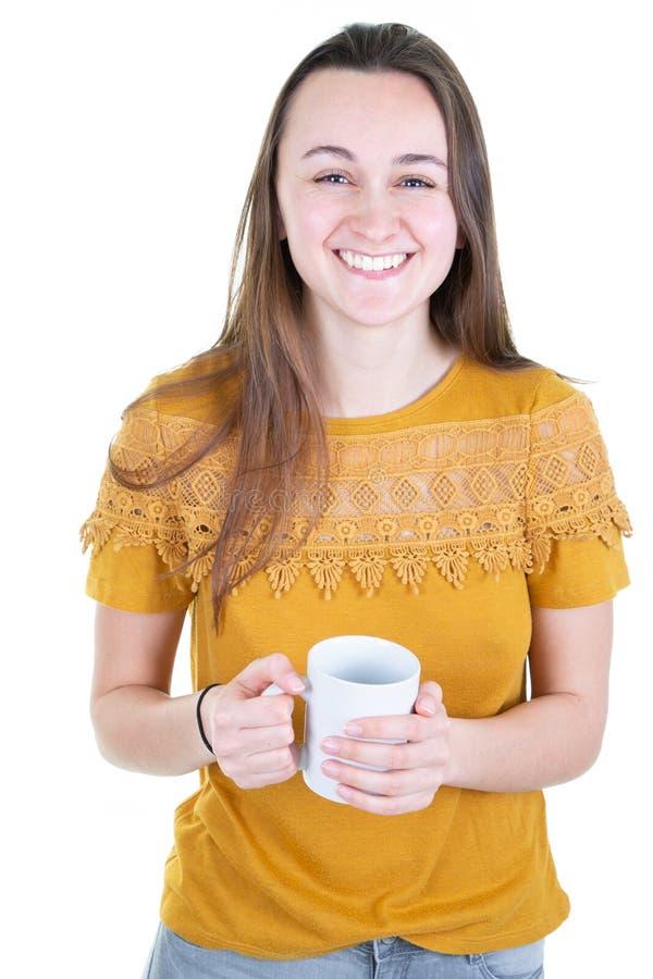 La mujer bonita sonriente feliz joven bebe un café en una taza blanca de la taza imagen de archivo