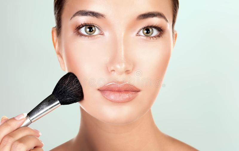 La mujer bonita sostiene el cepillo del maquillaje imagenes de archivo