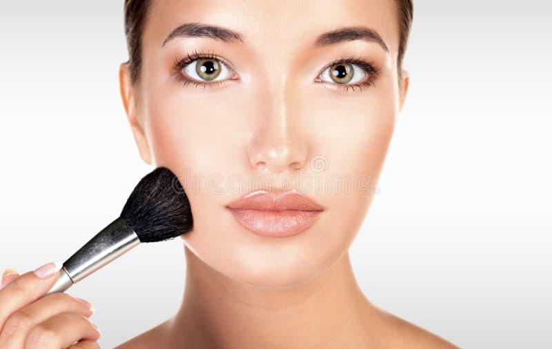 La mujer bonita sostiene el cepillo del maquillaje contra un fondo gris imagen de archivo libre de regalías