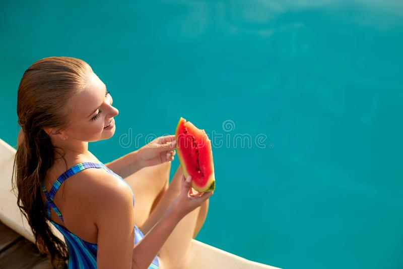 La mujer bonita sostiene la sandía roja de la rebanada que estira las piernas de largo bronceadas sobre la piscina azul, relajánd foto de archivo