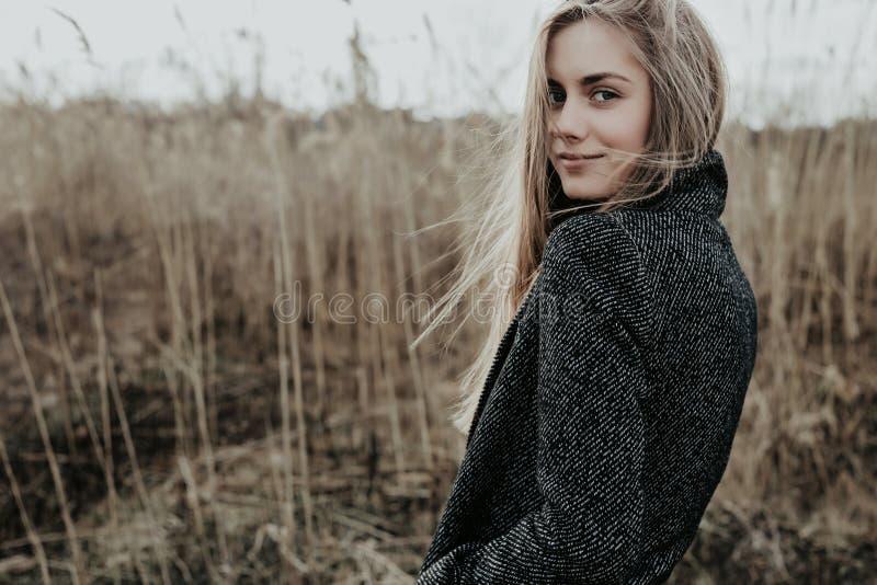 La mujer bonita y joven con el pelo rubio largo se vistió en la capa de las lanas que miraba la cámara sobre su hombro y sonrisa  imagen de archivo