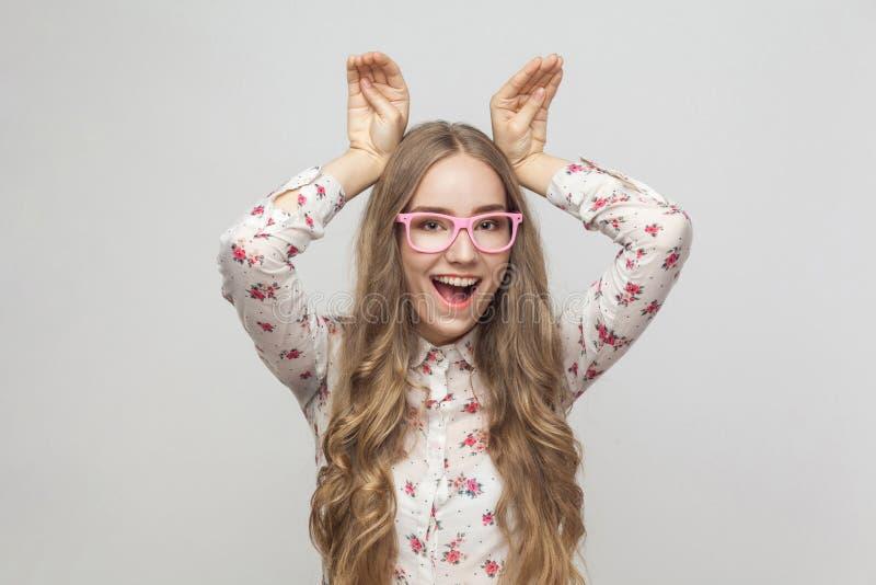 La mujer cómica en los vidrios rosados que llevan a cabo las manos mira el ` s como el oído de conejo imagen de archivo libre de regalías