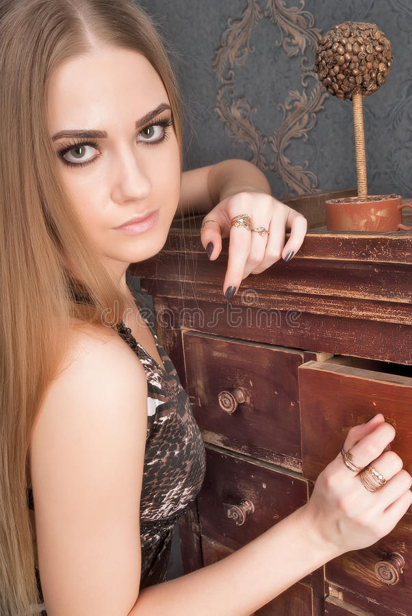 La mujer cabelluda rubia joven hermosa abre el cajón foto de archivo libre de regalías
