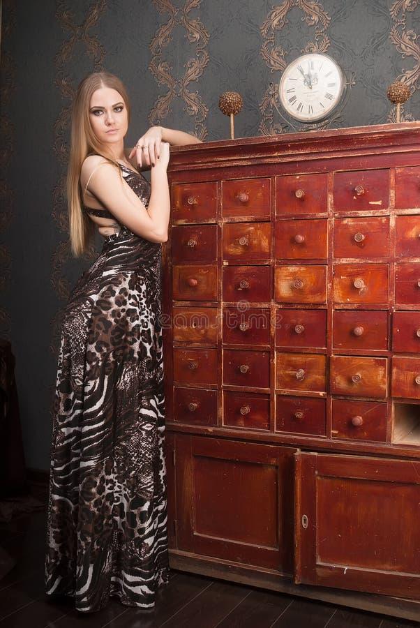 La mujer cabelluda rubia joven hermosa abre el cajón foto de archivo