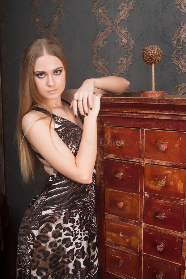 La mujer cabelluda rubia joven hermosa abre el cajón imagen de archivo libre de regalías