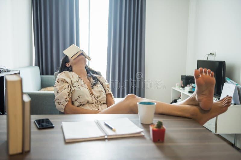 La mujer cansada toma una siesta después de leer foto de archivo