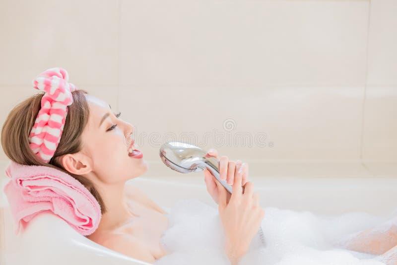 La mujer canta la canción en bañera imagenes de archivo