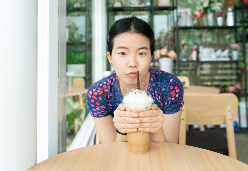 La mujer casual bonita asiática joven se sienta y sosteniendo una taza de café de hielo en la tabla de madera en cafetería fotografía de archivo libre de regalías