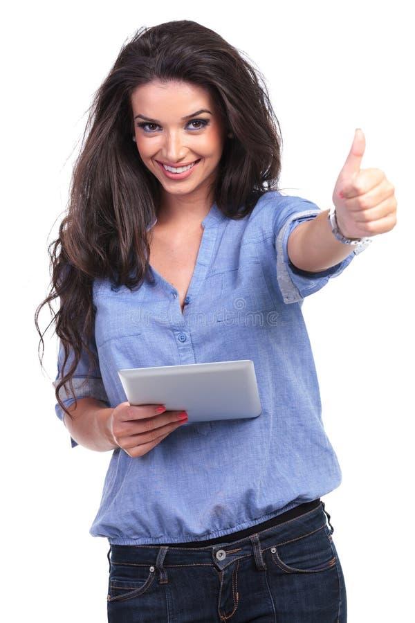 La mujer casual con la tableta muestra el pulgar para arriba fotografía de archivo libre de regalías