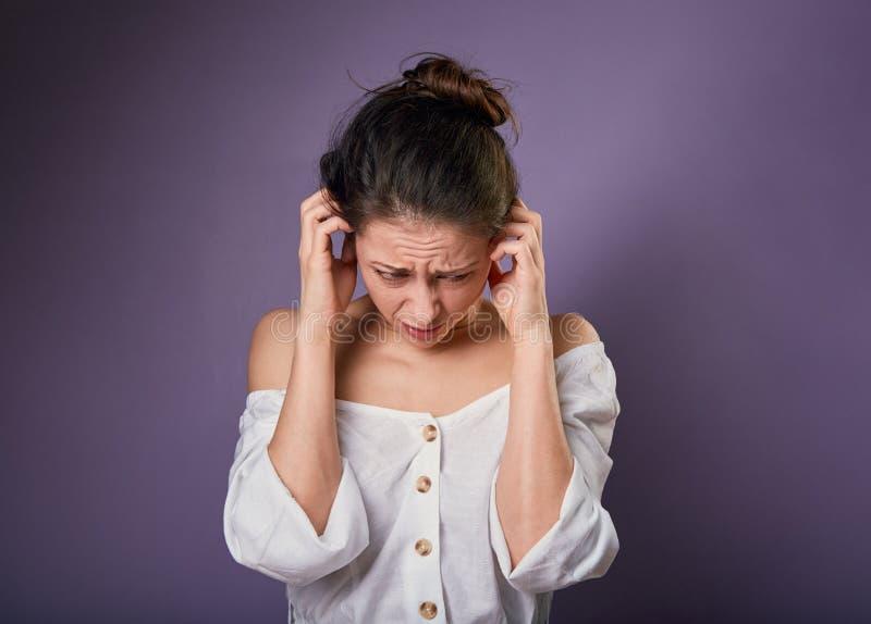 La mujer casual incierta subrayada cerró los oídos los fingeres porque no quiera oyen cualesquiera sonidos y ruido en fondo púrpu fotografía de archivo libre de regalías