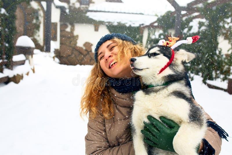 La mujer caucásica atractiva abraza el perro divertido del malamute que lleva las estimadas astas de la Navidad de santa Hembra s foto de archivo libre de regalías