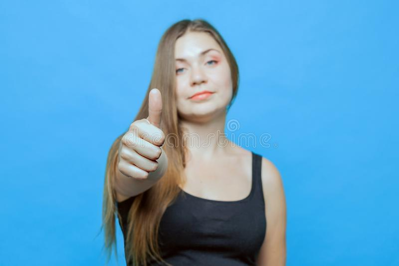 La mujer caucásica atractiva joven hace el pulgar para arriba, foco en el pulgar foto de archivo
