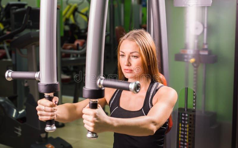 La mujer caucásica de la aptitud se está resolviendo en la máquina de la mariposa en gimnasio fotos de archivo libres de regalías
