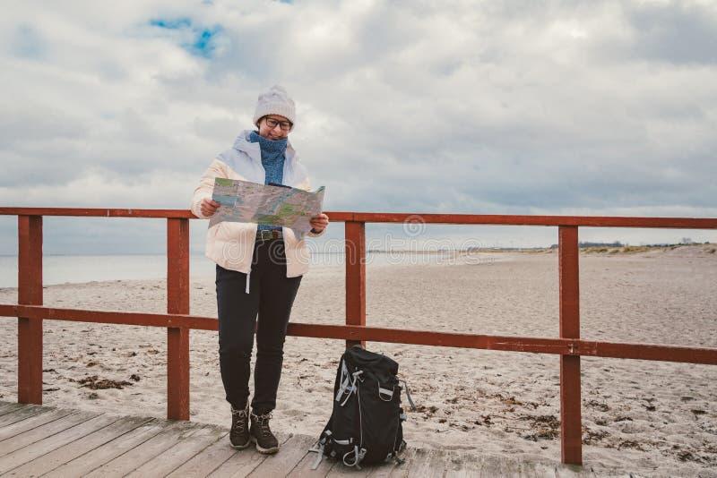 La mujer caucásica en sombrero y chaqueta con la mochila en invierno se sienta en el embarcadero de madera en la playa cerca de M imágenes de archivo libres de regalías
