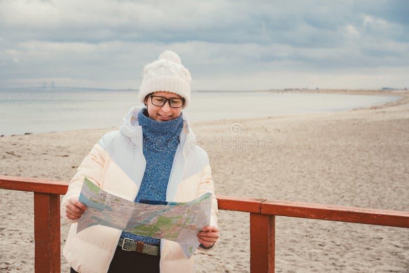 La mujer caucásica en sombrero y chaqueta con la mochila en invierno se sienta en el embarcadero de madera en la playa cerca de M fotografía de archivo
