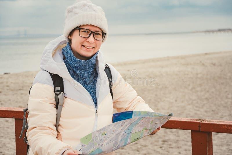 La mujer caucásica en sombrero y chaqueta con la mochila en invierno se sienta en el embarcadero de madera en la playa cerca de M fotos de archivo libres de regalías