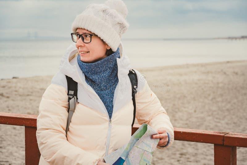 La mujer caucásica en sombrero y chaqueta con la mochila en invierno se sienta en el embarcadero de madera en la playa cerca de M fotos de archivo