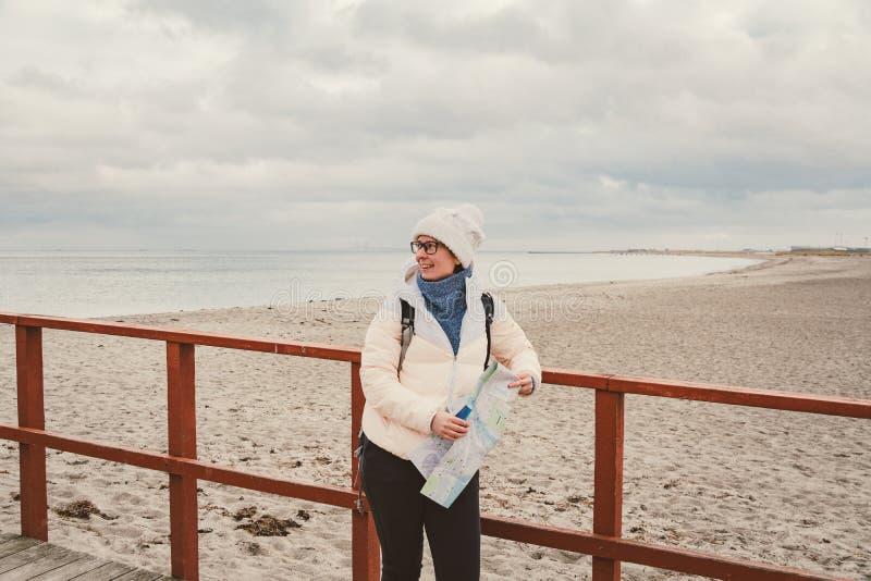La mujer caucásica en sombrero y chaqueta con la mochila en invierno se sienta en el embarcadero de madera en la playa cerca de M imagen de archivo libre de regalías