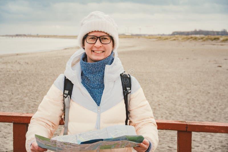 La mujer caucásica en sombrero y chaqueta con la mochila en invierno se sienta en el embarcadero de madera en la playa cerca de M fotografía de archivo libre de regalías
