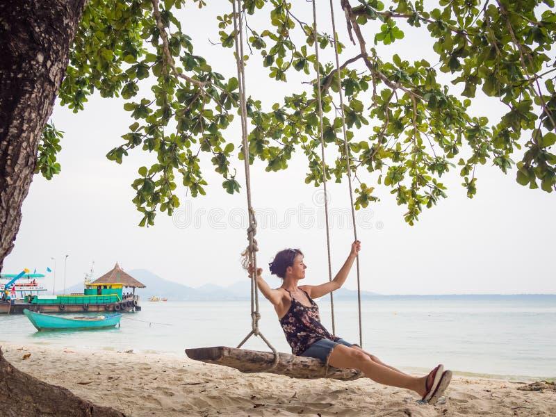 La mujer caucásica está balanceando en un oscilación de madera en la playa fotos de archivo libres de regalías