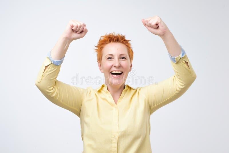 La mujer caucásica feliz con el pelo rojo exulta los puños de bombeo extáticos celebra éxito foto de archivo