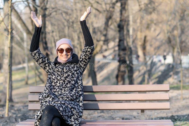 La mujer caucásica feliz hermosa en chaqueta, el sombrero y las gafas de sol gozan el sentarse en banco en el parque o el bosque  fotografía de archivo libre de regalías