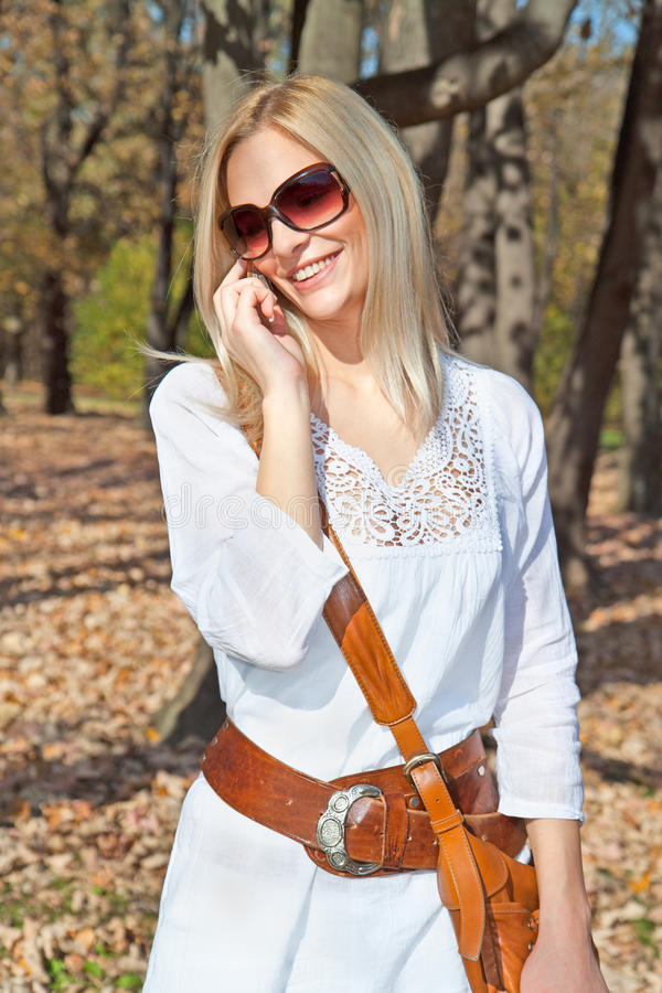 La mujer caucásica hermosa feliz tiene una llamada de teléfono foto de archivo