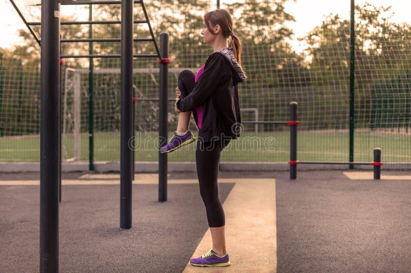 La mujer caucásica joven calienta en la tierra de deporte del parque La muchacha en los deportes plantea la pierna para arriba en imagen de archivo