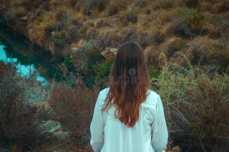 La mujer caucásica joven con el pelo largo de la castaña en la camisa de lino blanca mira el río que se coloca en prado del campo imagen de archivo libre de regalías
