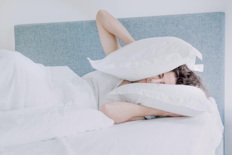 La mujer caucásica joven con el pelo negro duerme presionando las almohadas a sus oídos y cabeza fotografía de archivo libre de regalías