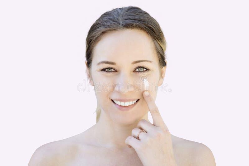 La mujer caucásica joven mancha una loción facial en su mejilla después de un Showe fotos de archivo