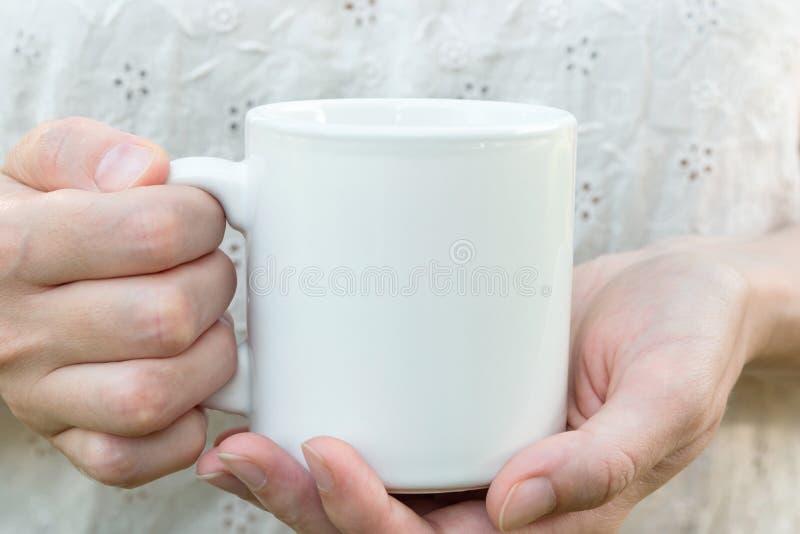La mujer caucásica joven que sostiene una taza blanca, imita para arriba, espacio en blanco para el texto, ilustraciones, manos,  foto de archivo