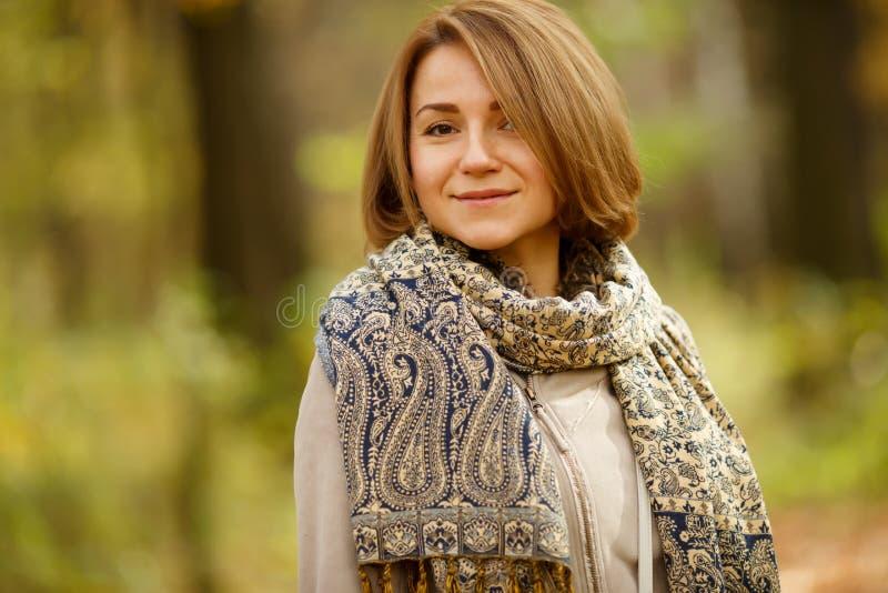 La mujer caucásica joven sonriente en otoño caliente cubre y bufanda fotografía de archivo