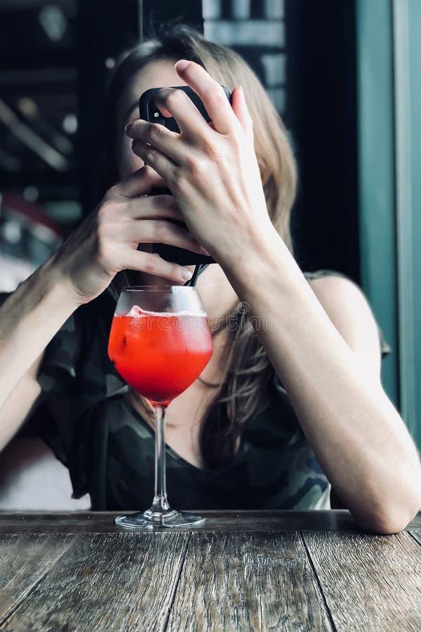 La mujer caucásica joven sostiene el teléfono elegante delante de la cara que se sienta en la tabla en el café, bocal con el cóct imagen de archivo libre de regalías
