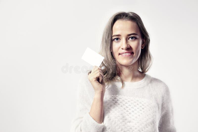 La mujer caucásica joven sostiene la tarjeta de visita en blanco disponible imagen de archivo libre de regalías
