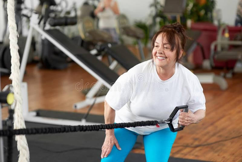 La mujer caucásica mayor entrena a sus brazos en el gimnasio imágenes de archivo libres de regalías