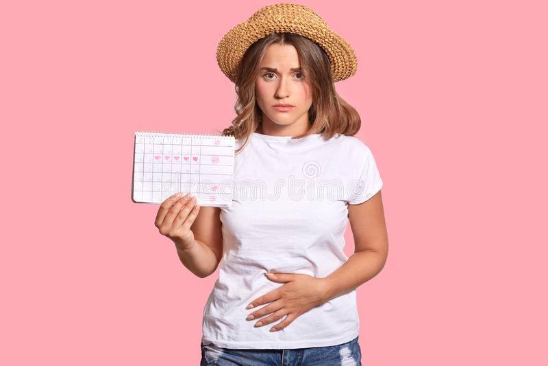 La mujer caucásica trastornada guarda la mano en el estómago, lleva la camiseta blanca casual y el sombrero de paja, sostiene el  foto de archivo libre de regalías