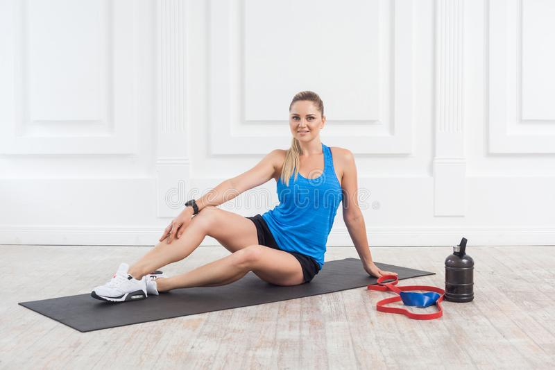 La mujer causcasian atlética joven hermosa satisfecha feliz en pantalones cortos negros y la localización superior azul y tienen  imagen de archivo libre de regalías