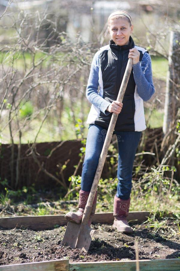 La mujer cava la tierra en el jardín fotografía de archivo libre de regalías