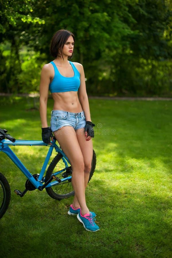 La mujer cerca de la bici imágenes de archivo libres de regalías