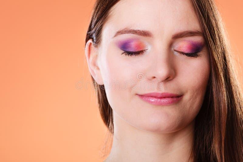 La mujer cerrada observa el retrato colorido del maquillaje foto de archivo
